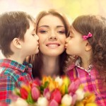 Mamá con dos hijos besándola