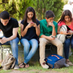 29348172 - group of teenage boys and girls ignoring each other while using their cell phones at school