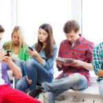 37106963 - education and internet concept - students looking at their phones and tablet pc at school