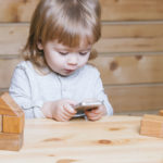 55567749 - cute funny little baby boy with long blonde curly hair playing on computer and mobile phone near toy building blocks indoor on wooden background, horizontal picture